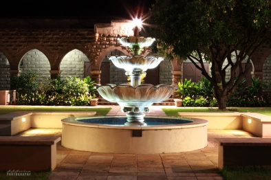 The fountain of Sacred Heart Church lit up at night.